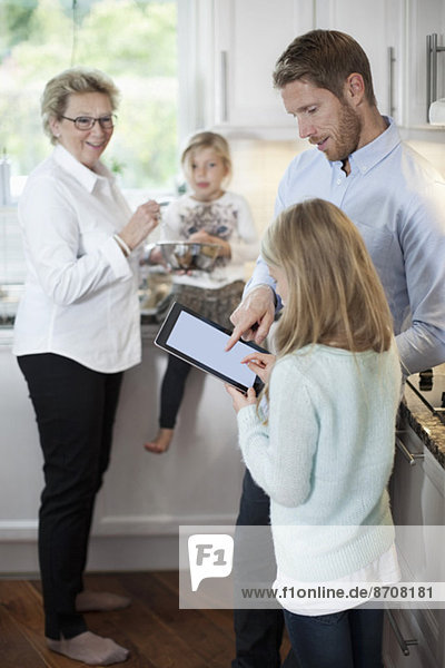 Familie mit digitalem Tablett beim Kochen in der Küche