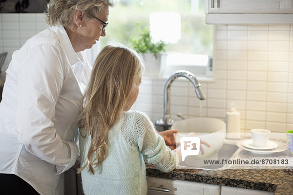 Großmutter und Enkelin beim Gemüsewaschen in der Küche