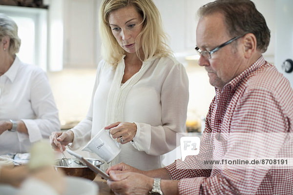 Woman looking at father-in-law using digital tablet while cooking in kitchen