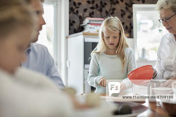 Mädchen schneiden Gemüse beim Kochen mit der Familie in der Küche