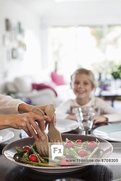 Abgeschnittenes Bild einer Frau  die am Esstisch Salat serviert.