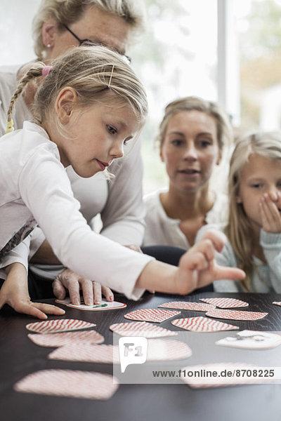 Mädchen spielen Kartenpuzzlespiel mit der Familie zu Hause