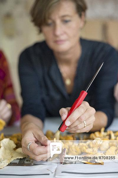 Reife Frau reinigt Pfifferlinge zu Hause