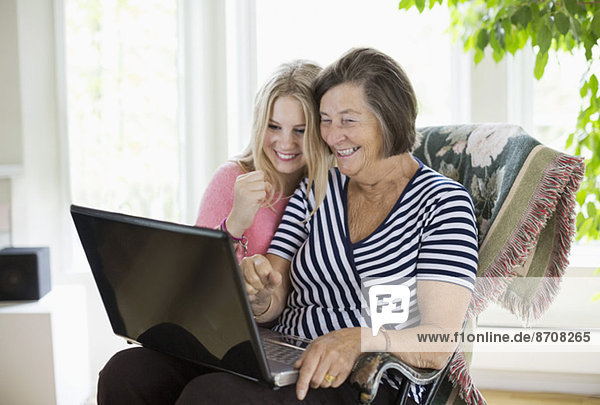 Glückliche Großmutter und Enkelin mit Laptop zu Hause
