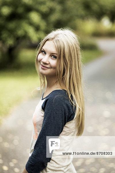 Porträt eines lächelnden Mädchens  das auf der Straße steht.