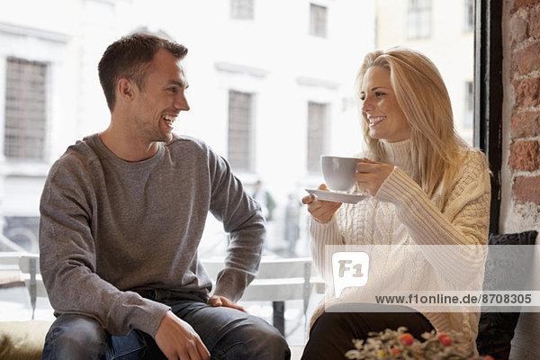 Glückliches junges Paar verbringt seine Freizeit im Cafe
