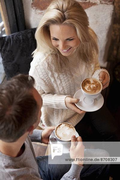 Hochwinkelansicht des jungen Paares beim Kaffee im Cafe