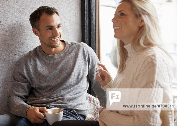 Ein glückliches junges Paar verbringt seine Zeit im Café.