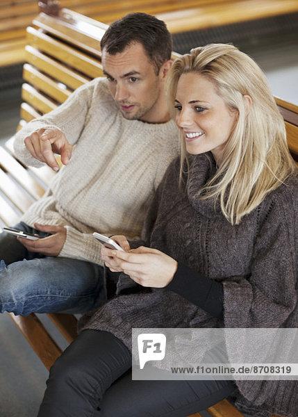 Glückliches junges Paar mit Mobiltelefonen auf der Fähre