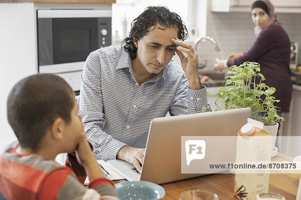 Muslimischer Mann bei der Arbeit am Laptop mit Familie in der Küche