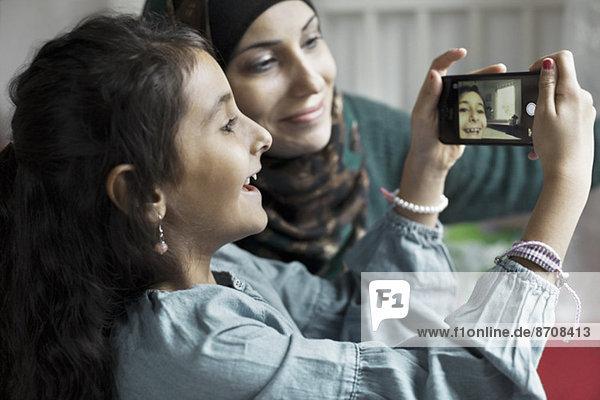 Mutter und Tochter beim Selbstporträt im Schlafzimmer