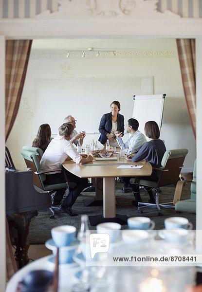Blick auf die Geschäftsleute in der Konferenz durch die Türöffnung