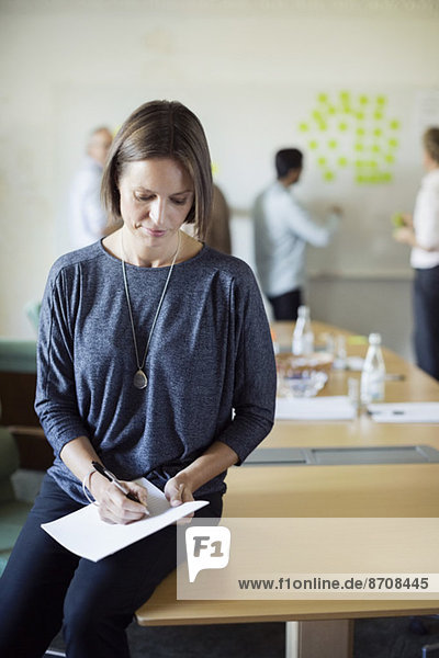 Geschäftsfrau beim Schreiben von Dokumenten im Konferenzraum mit Kollegen  die im Hintergrund diskutieren.