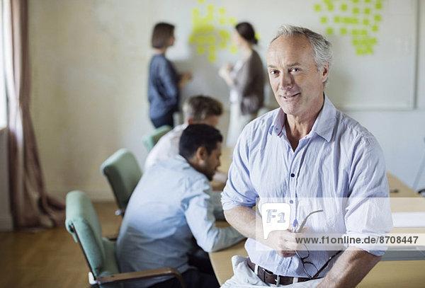 Portrait eines selbstbewussten Geschäftsmannes am Konferenztisch mit Kollegen  die im Hintergrund diskutieren.