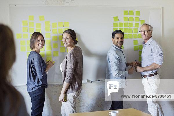 Fröhliche Geschäftsleute am Whiteboard im Büro