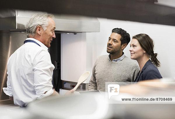 Koch im Gespräch mit Geschäftsleuten in der Großküche
