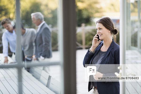 Geschäftsfrau mit Handy auf der Terrasse mit Kollegen im Hintergrund