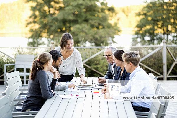 Gruppe von Geschäftsleuten  die am Tisch auf der Terrasse arbeiten