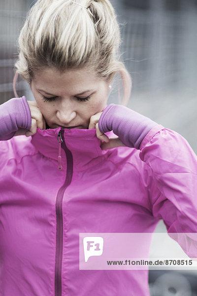 Sportliche Frau  die den Kragen der Jacke anpasst.