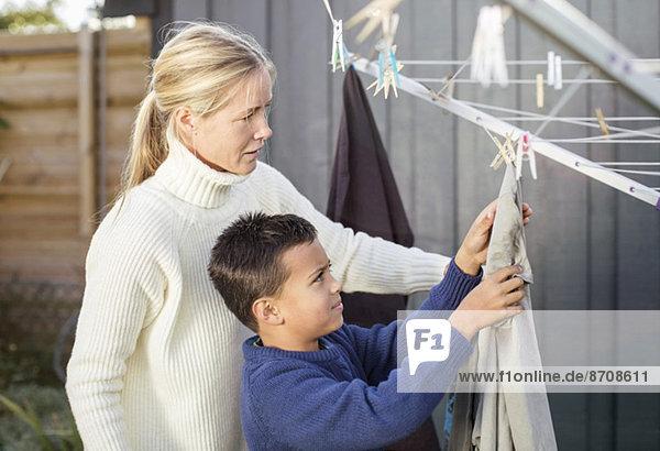 Mutter und Sohn beim Wäschewaschen im Hof