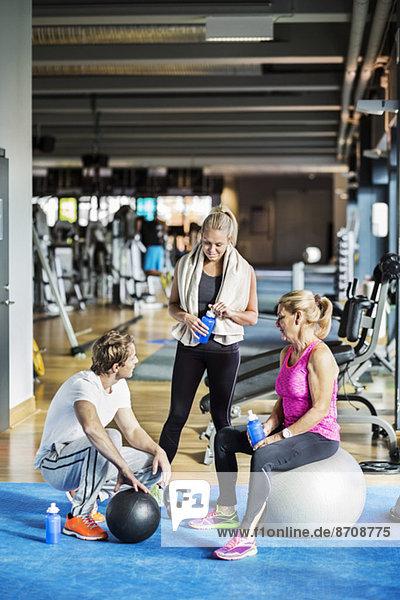 Freunde  die sich im Fitnessstudio unterhalten