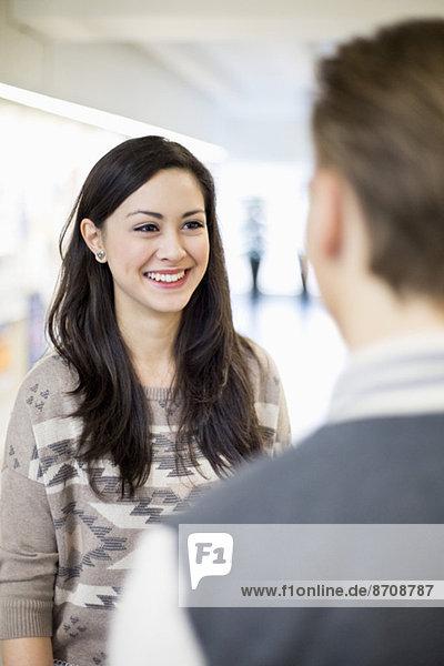 Glückliche Studentin im Gespräch mit einer Freundin im College
