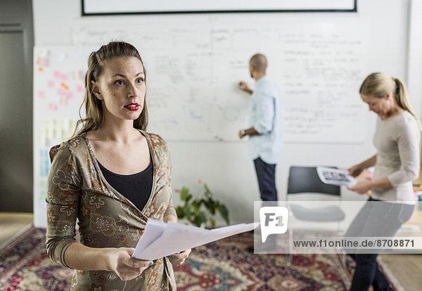 Geschäftsfrau mit Dokumenten  während Mitarbeiter im Hintergrund im Büro arbeiten
