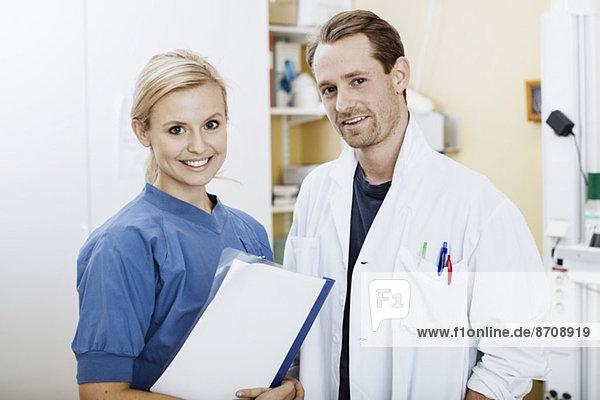 Porträt des selbstbewussten Arztes und der Krankenschwester mit Akte im Krankenhaus