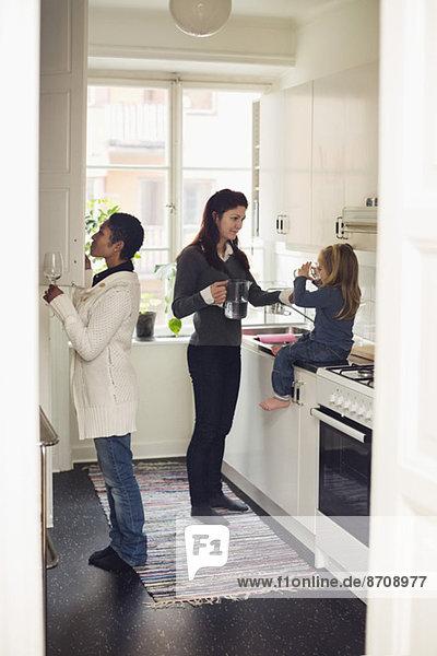 Volle Länge des lesbischen Paares mit Mädchen in der Küche