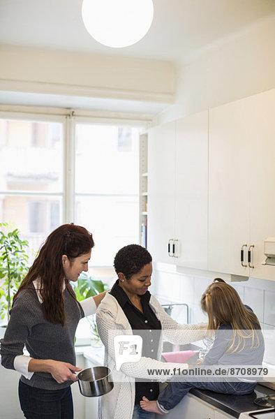 Mädchen mit lesbischem Paar in der Küche
