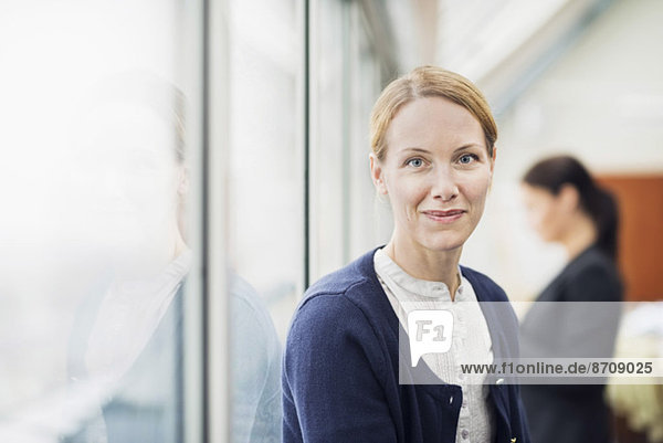 Portrait of confident businesswoman with colleague in background at office