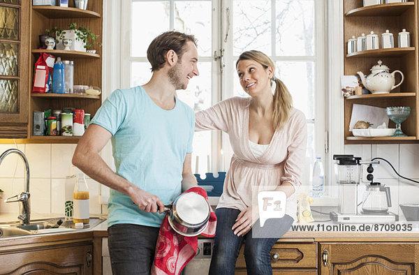 Mann wischt den Topf ab  während er die Frau sieht  die auf der Küchentheke sitzt.