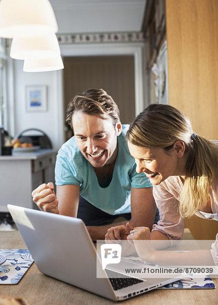 Glückliches Paar beim Spielen auf dem Laptop am Tisch