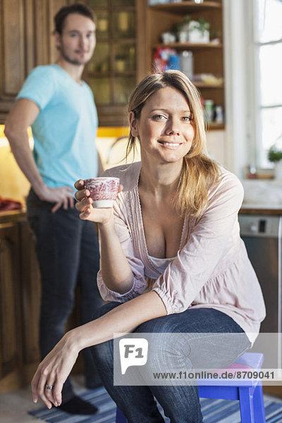 Porträt der Frau mit Kaffeetasse und Mann im Hintergrund in der Küche