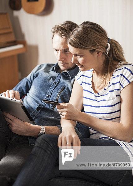 Online-Einkaufen mit Kreditkarte und digitalem Tablett zu Hause