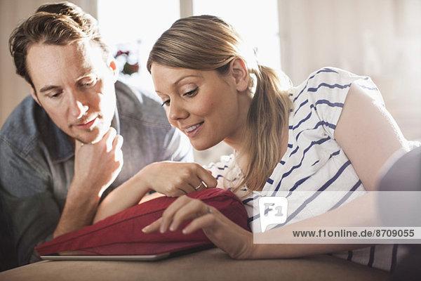 Mittleres erwachsenes Paar mit digitalem Tablett im Haus