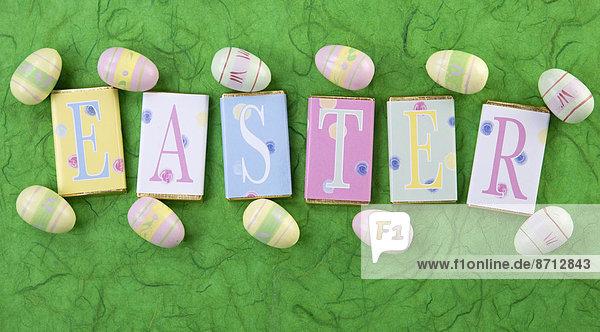 Buchstabe klein grüßen grün Verpackung Hintergrund Schokolade Süßigkeit Wort Osterei Ostern umwickelt