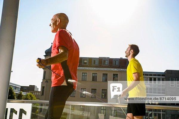 Zwei männliche Athleten trainieren mit Springseilen auf dem Stadtdach