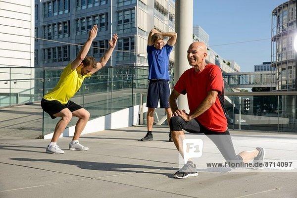 Drei männliche Athleten trainieren auf dem Dach der Stadt