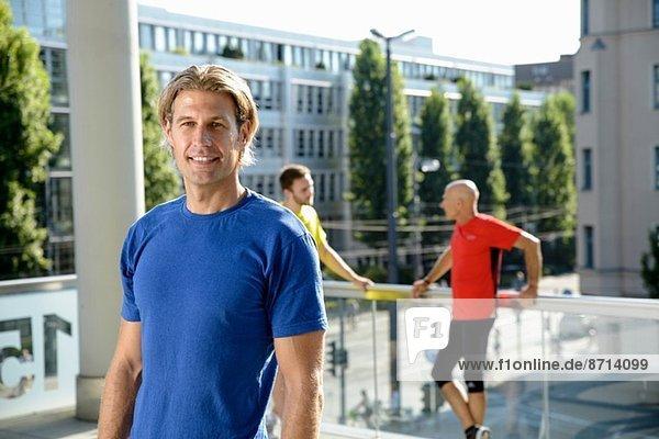 Mittlerer Erwachsener  männlicher Trainer und Klasse  die eine Pause auf dem Dach der Stadt einlegen.