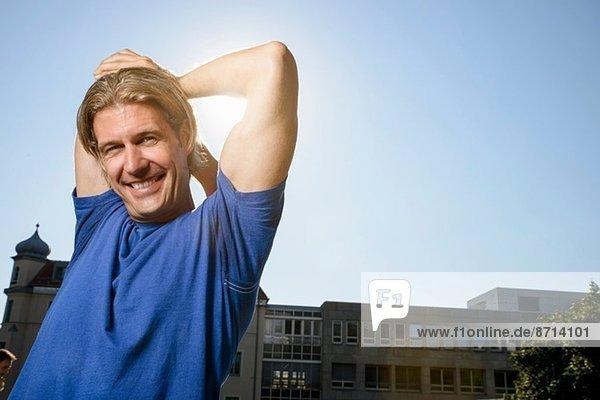 Mittlerer Erwachsener Mann  der sich während des Trainings auf dem Dach der Stadt ausdehnt.