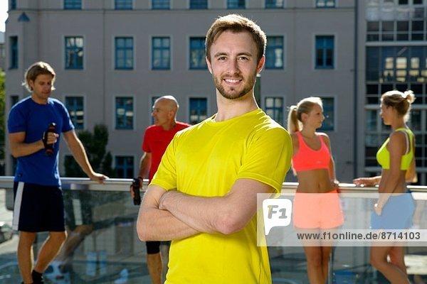 Junge männliche Trainerin und Klasse bei einer Pause auf dem Stadtdach