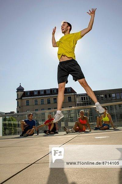 Junge männliche Trainerin feiert vor der Klasse auf dem Stadtdach