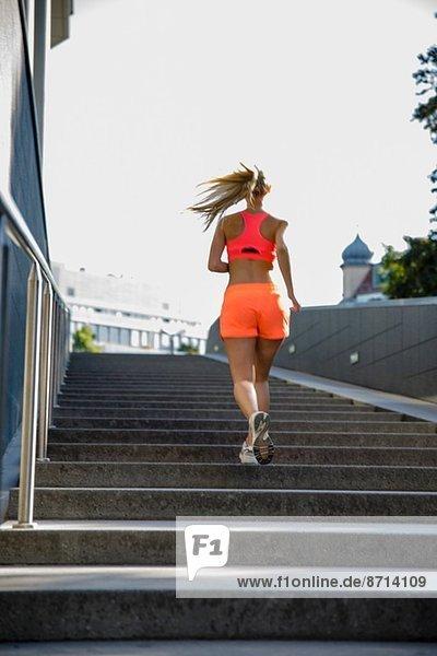 Junge Läuferin auf der Stadttreppe