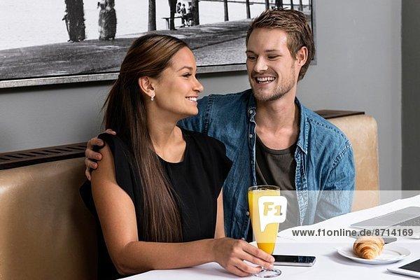 Junges Paar sitzt im Cafe mit Technik auf dem Tisch