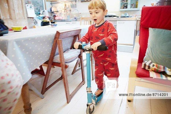 Junge spielt auf dem Roller in der Küche