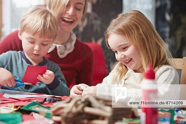 Mother and two children crafting at kitchen table