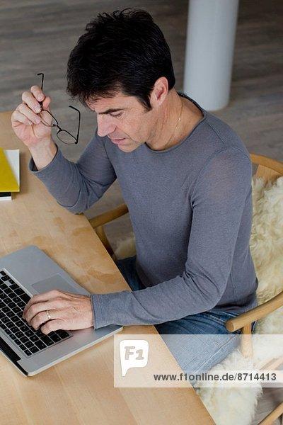 Mature businessman working an laptop at home