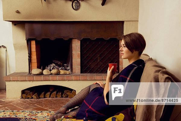 Young woman sitting on sofa wrapped in a blanket