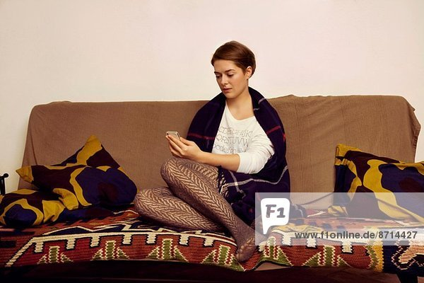 Young woman sitting on sofa texting on cellphone